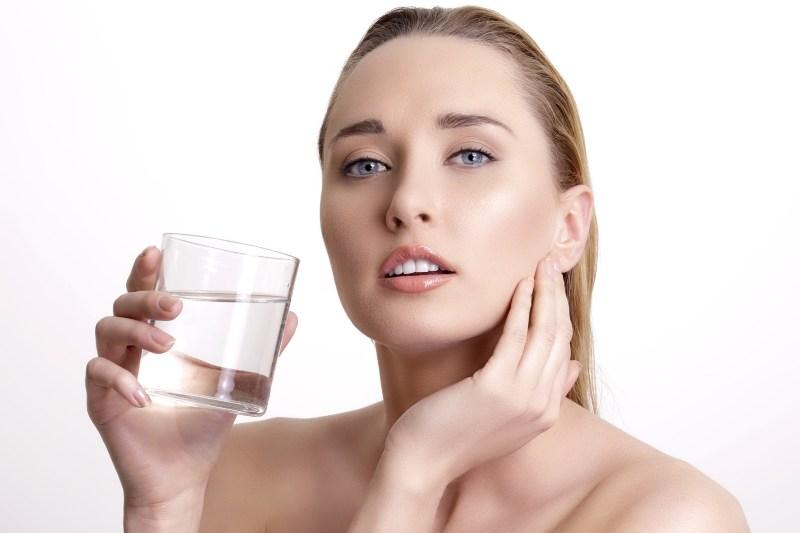beautiful young beautiful woman drinking fresh water on white